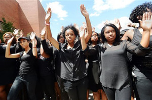 "Law students at North Carolina Central University including Chenae Hammond, center, walk in the ""hands up, don't shoot"" posture during a rally to protest the shooting death of Michael Brown by a white police officer in Ferguson, Mo.,Monday, Aug. 25, 2014, at the Turner Law Building at North Carolina Central University, in Durham. (AP Photo/The Herald-Sun, Bernard Thomas)"