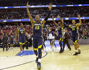 Marquette guard Vander Blue (13) celebrates with center Chris Otule (42), Jamil Wilson (0) and guard Trent Lockett (22) after their 71-61 win over Miami in an East Regional semifinal in the NCAA college basketball tournament, Thursday, March 28, 2013, in Washington. Blue scored 14 points, and Wilson led all scorers with 16 points. (AP Photo/Alex Brandon)