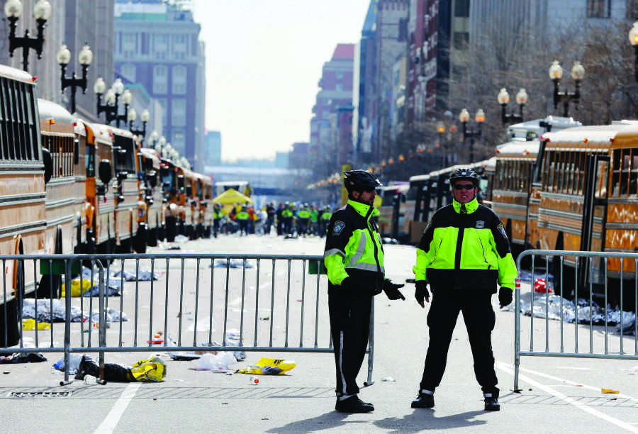 Boston police officers stand on Boylston Street near empty buses meant to transport runners who were instead diverted from the course following an explosion at the finish line, Monday. Photo by Michael Dwyer/The Boston Globe/Associated Press