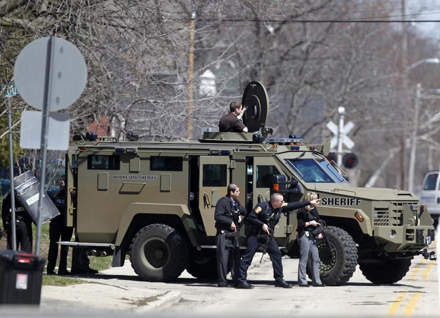 Police and sheriff's deputies stand ready  in Waukesha, Wis., Tuesday April 16, 2013, as Caroll University was put on lockdown after a gunman was spotted near the campus. A man was led away in handcuffs from a nearby apartment building and the lockdown was lifted. (AP Photo/ Milwaukee Journal-Sentinel, Kristyna Wentz-Graff)