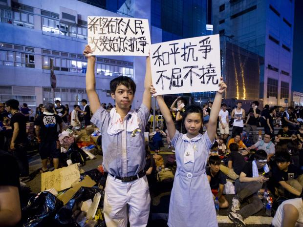 High school demonstrators hold signs during a protest outside the headquarters of Legislative Council in Hong Kong on Sept. 29, 2014.  Photo via nationalpost.com/XAUME OLLEROS/AFP/Getty Images