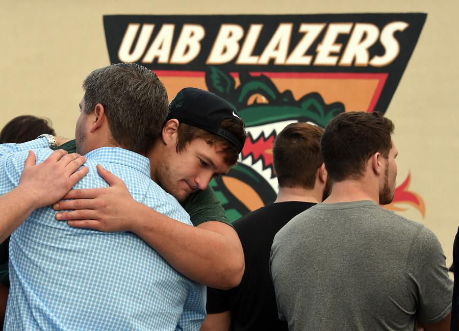 UAB offensive tackle Steve Pickern hugs UAB supporter Justin Craft  after UAB President Ray Watts announced the shut down of the UAB football program Tuesday, Dec. 2, 2014 in Birmingham, Ala. UAB is shutting down the football program after one of the Blazers' stronger seasons.  The university announced the decision Tuesday minutes after President Ray Watts met with the Blazers players and coaches, while several hundred UAB students and fans gathered outside for the third straight day in efforts to support the program. (AP Photo/AL.com, Joe Songer)