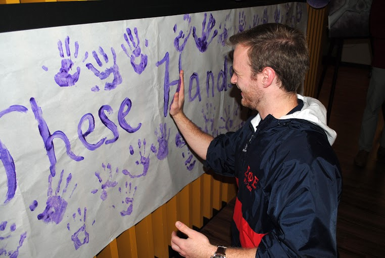 Student adds hand print to