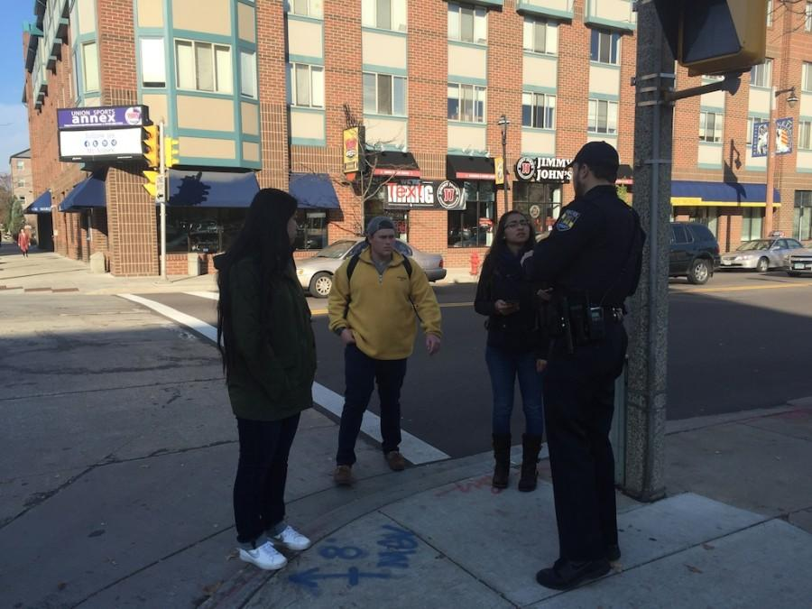 Officer Brian Plachinski hands out pizza coupons to students who followed pedestrian rules. Photo courtesy of Jeff Kranz.