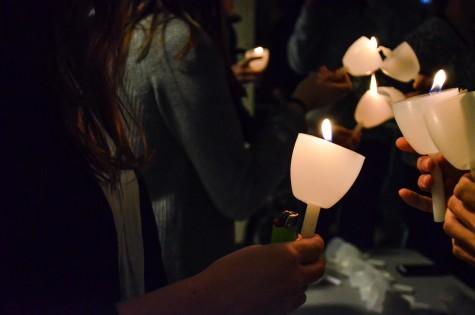 Students light each others candles at the vigil. Photo by Matt Serafin /matthew.serafin@mu.edu
