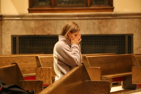 A student prays at the memorial Mass. Photo by Yue Yin/ yue.yin@marquette.edu