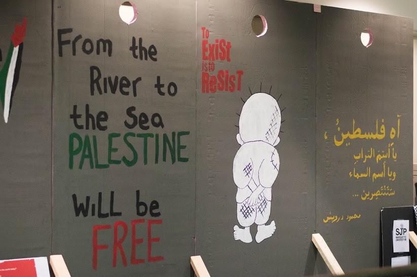 "The wall displays symbolic images and statements about the Israeli-Palestine conflict, including ""to exist is to resist."" Photo by Meredith Gillespie/meredith.gillespie@marquette.edu"