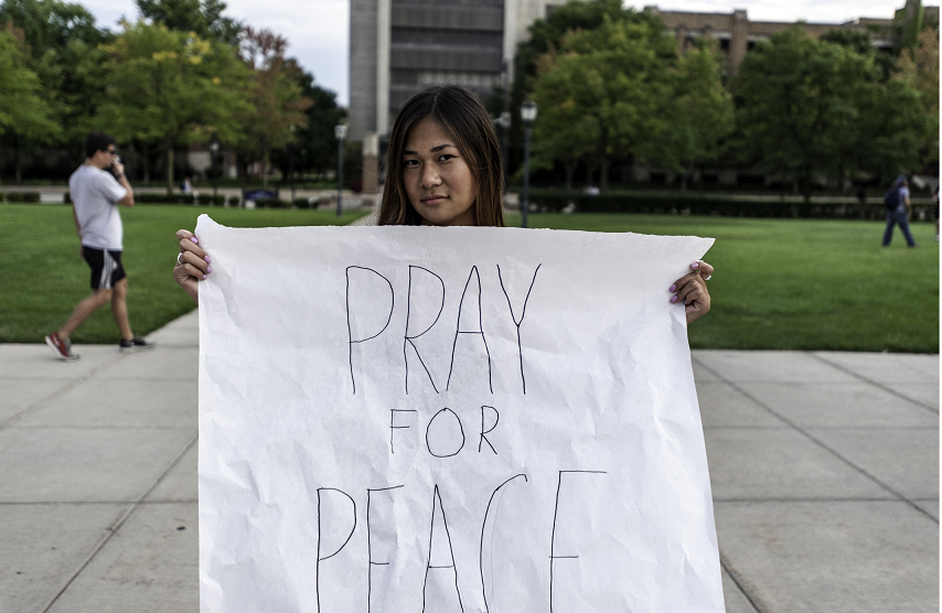 A Marquette student holds a sign that demonstrates her plea for peace. Photo by Michael Carpenter