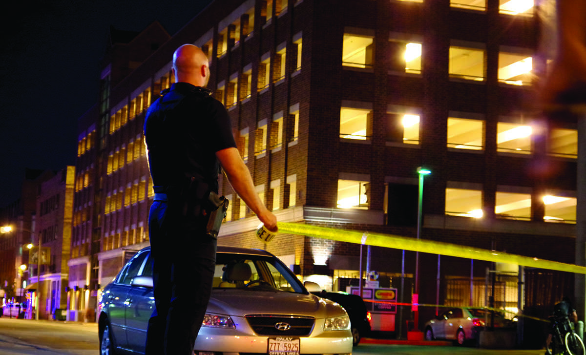 A Marquette University police officer looks up at the parking structure where the student was standing on the ledge. Photo by Jennifer Walter/jennifer.walter@marquette.edu
