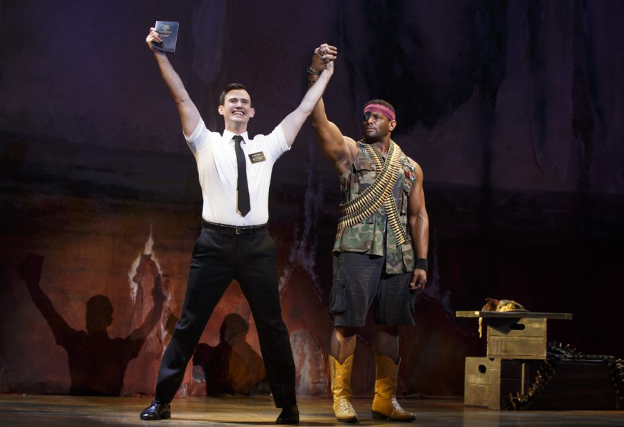 Ryan Bondy (Elder Price) and Tommar Ommar Wilson (Ensemble) hold hands in triumph during a scene.