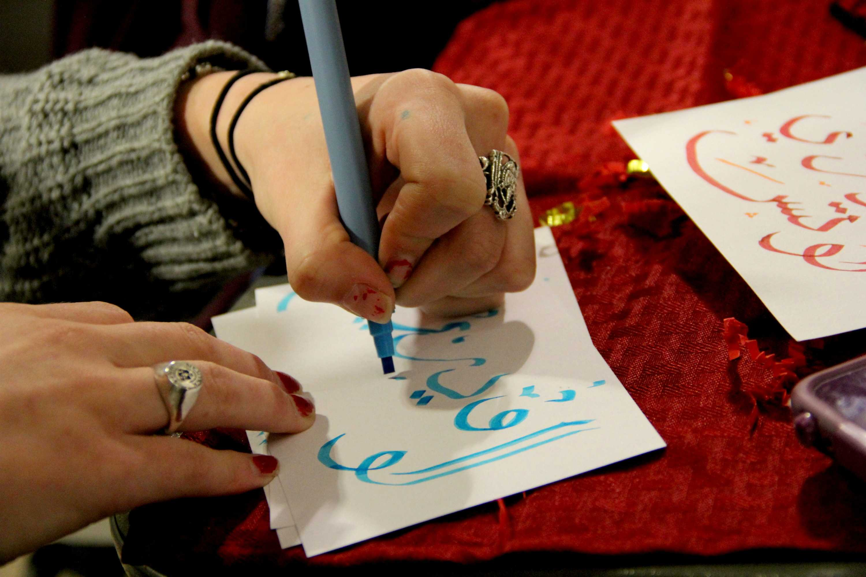 Arabic Language and Culture Club member Audrey Lodes practices Arabic calligraphy. Wire Stock Photo