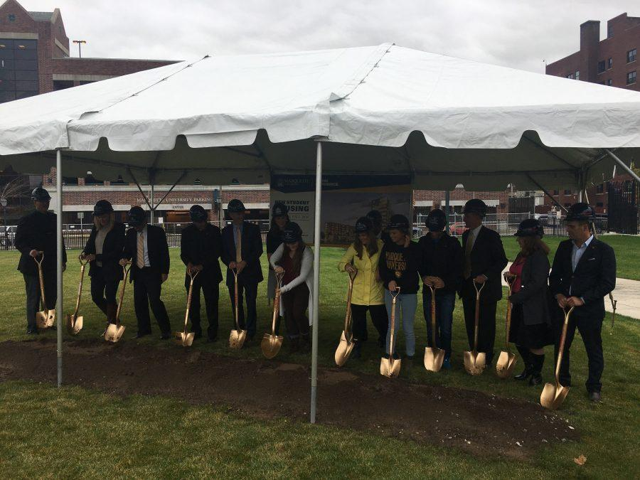 Students and faculty participate in ground-breaking ceremony in front of O'Donnell Hall.