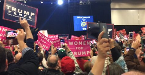 Audience members wave their signs in anticipation for President-Elect Donald Trump to take the stage.