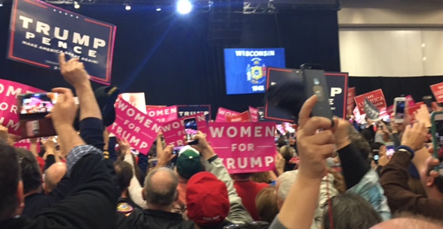 Audience+members+wave+their+signs+in+anticipation+for+President-Elect+Donald+Trump+to+take+the+stage.+