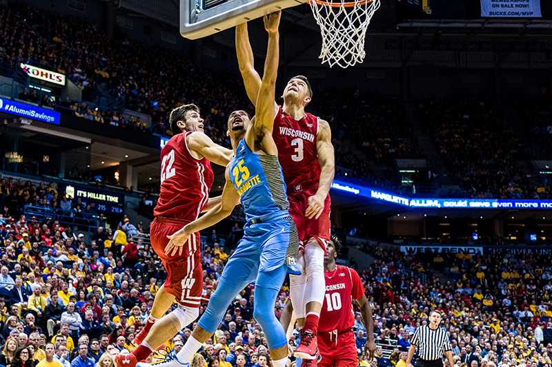Wisconsin's Ethan Happ (left) and Zak Showalter (right) defend Haanif Cheatham during the second half.