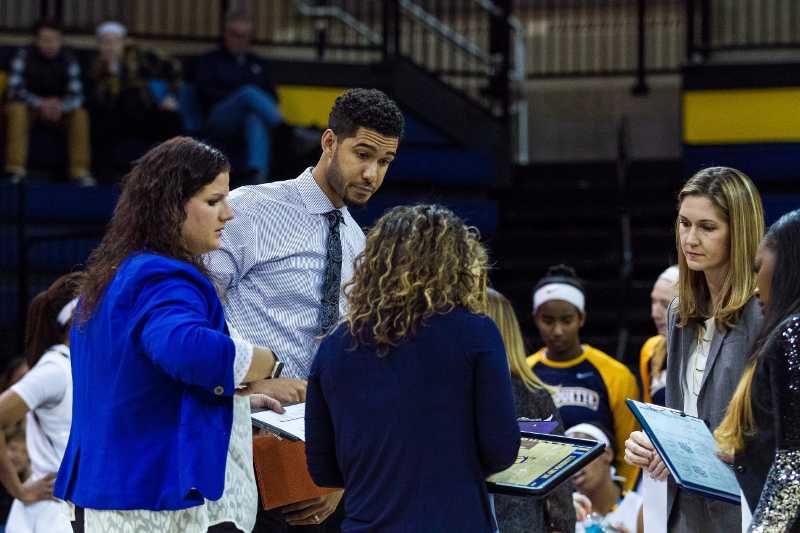 Scott+Merritt+%28center%29+stands+with+the+rest+of+women%27s+basketball%27s+coaching+staff.