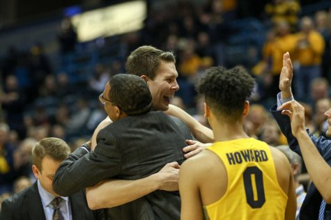 Matt Heldt hugs assistant coach Chris Carrawell after coming off the court in Marquette