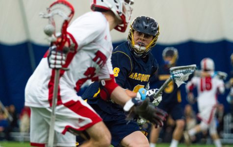 Nick Grill guards a Detroit Mercy attackman during Marquette's game Sunday.