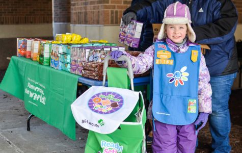 Julianna Tarpinian-Kitelinger, a Daisy Girl Scout, shows off her delivery cart. She sells door-to-door and also at booths.