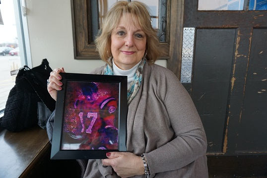 Claire Schuster holds a picture of her son, Tim.