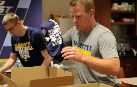 Cole Bovard a sophomore in the College of Arts & Sciences and coach Steve Wojciechowski send supplies to victims in Houston.   Photo courtesy of Marquette Athletics