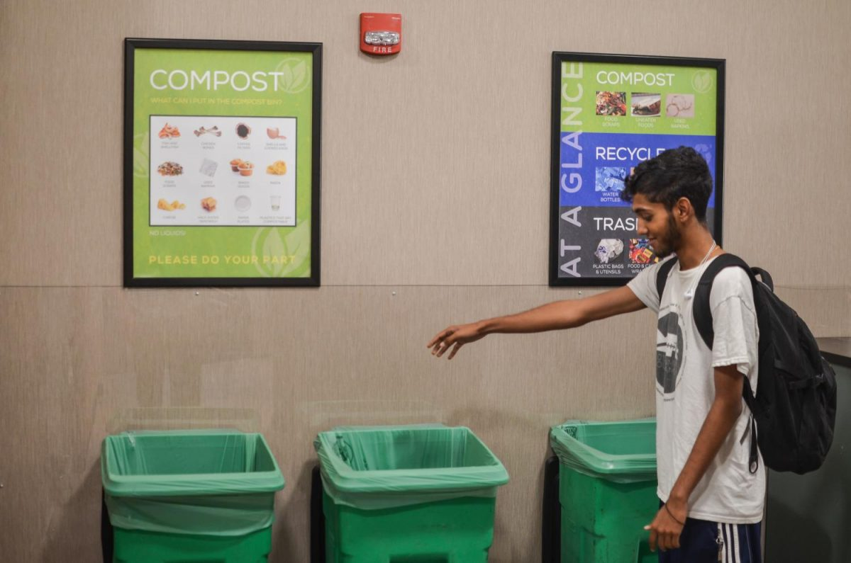 Justin+Kollamana%2C+a+freshman+in+the+College+of+Arts+%26+Sciences%2C+uses+the+compost+bin+in+Straz+Hall.+