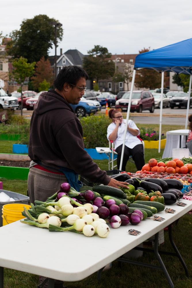 A customer looking at fresh produce at the Near West Side farmers market.