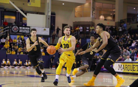 Senior guard Andrew Rowsey drives past two UW-Milwaukee defenders Sunday night. Rowsey finished with a double-double, 12 points and 11 assists in Marquette's 78-63 exhibition win. (Photo by Maggie Bean)