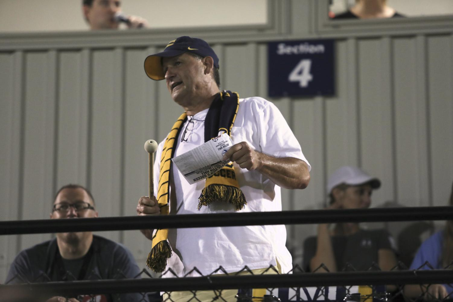 David Heim, also known as Drum Guy, yells encouragement to the men's soccer team.
