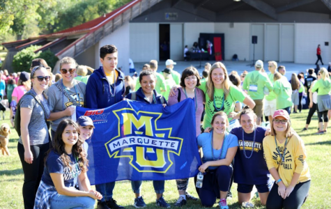 Marquette students pose by an MU flag.