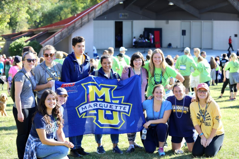 Marquette+students+pose+by+an+MU+flag.