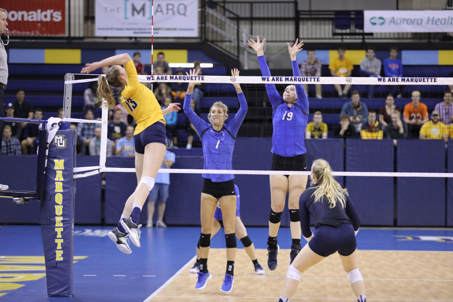Outside hitter Anna Haak elevates for an attack against a double block.