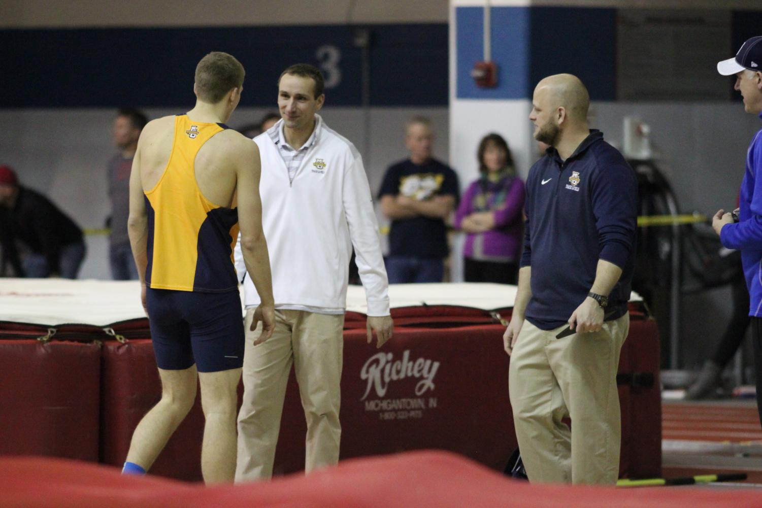 Track and field assistant coach Rick Bellford (center) works with former All-American high jumper Wally Ellenson. (Photo by Maggie Bean, courtesy of Marquette Athletics.)