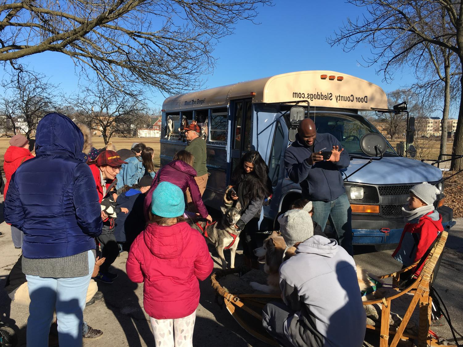 People congregate around the Sled Dogs of Door County and their vehicle at a
