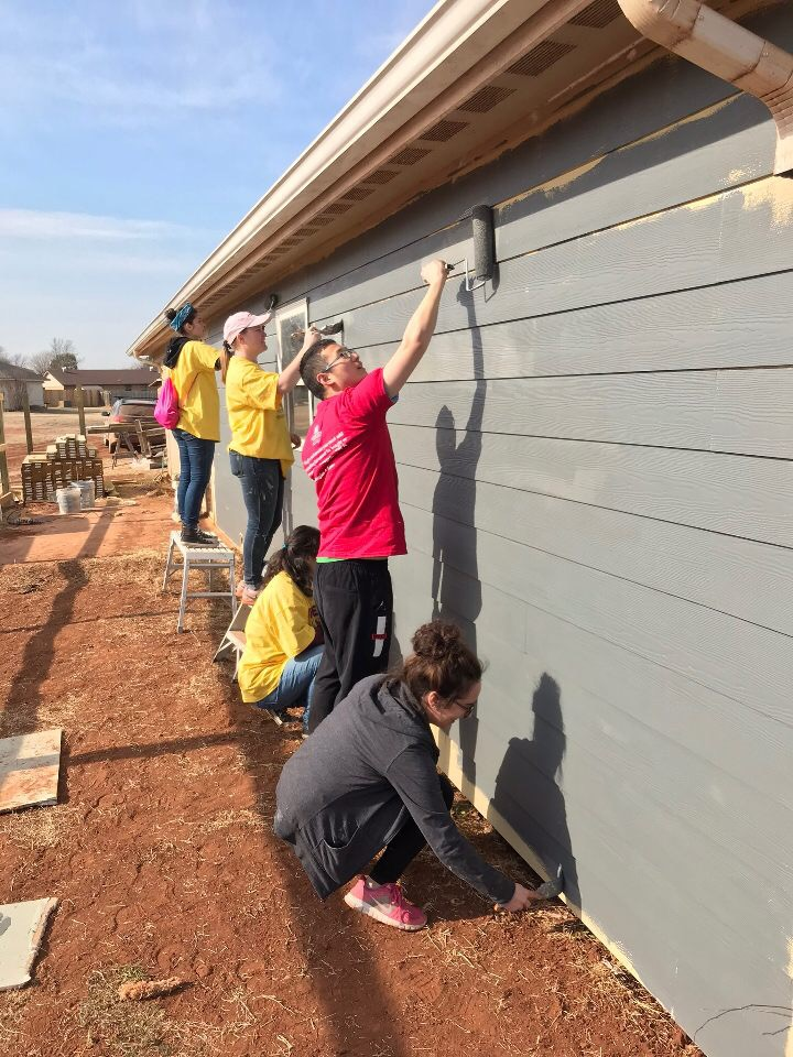 Students work on painting the exterior of a house in Enid, Oklahoma on a Marquette Action Program trip.