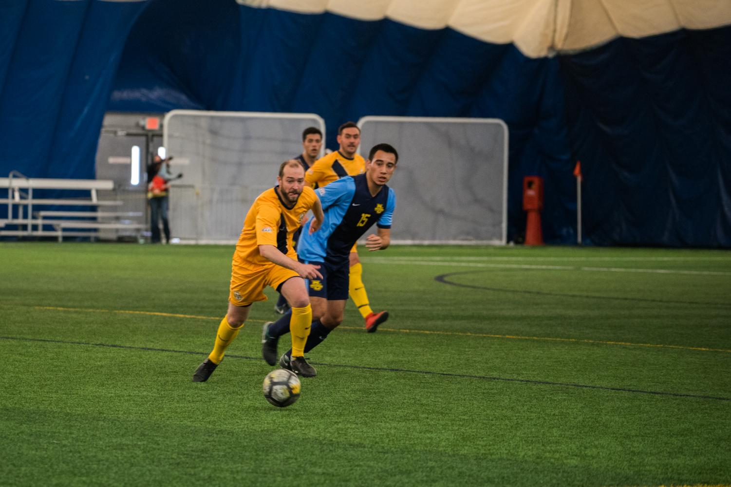 Nathan Sabich (left) goes for the ball in the men's soccer alumni game. Sabich played at Marquette from 2003 to 2006.