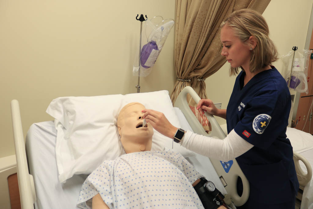 Nursing student practices medical procedure on dummy.
