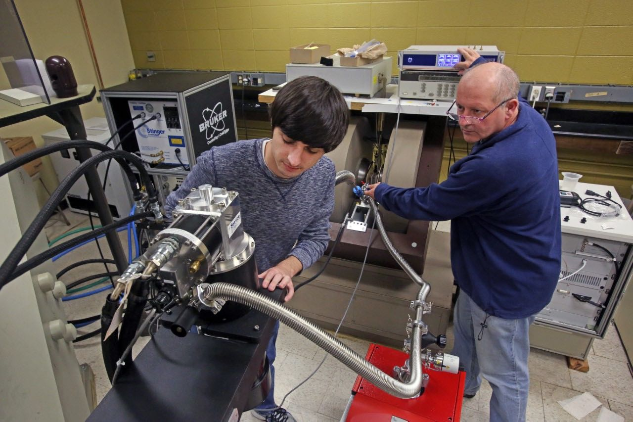 Former undergraduate student, Anthony Franciso and Dr. Brian Bennett use EPR machine.