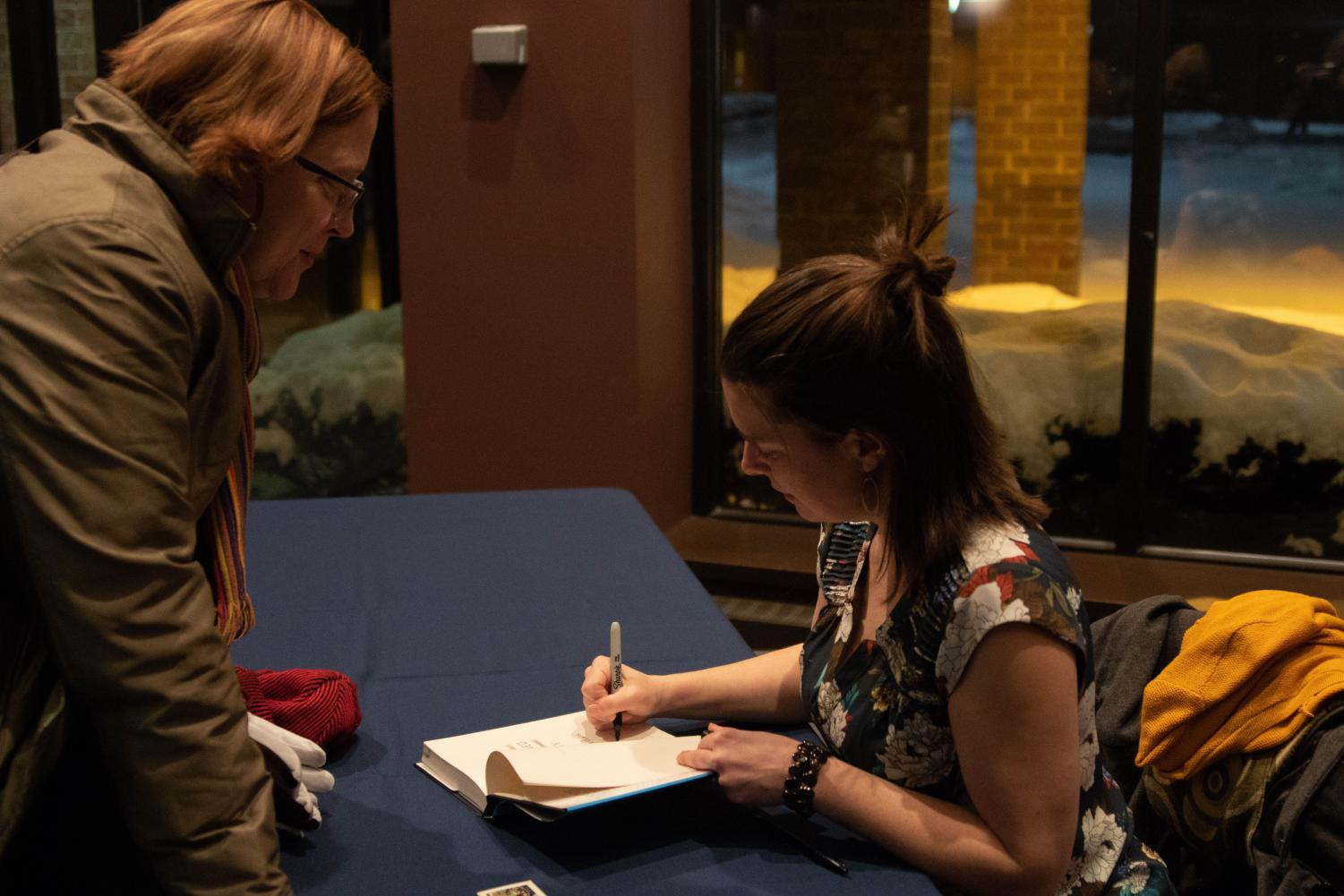 Anna Clark signs a copy of her book