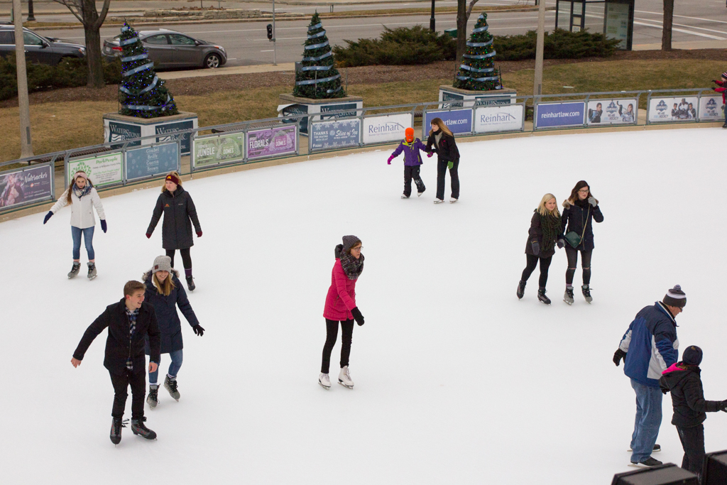 Skaters of various ages enjoy Red Arrow Park's Slice of Ice, an ice rink located in downtown Milwaukee with free admission and $9 skate rentals.