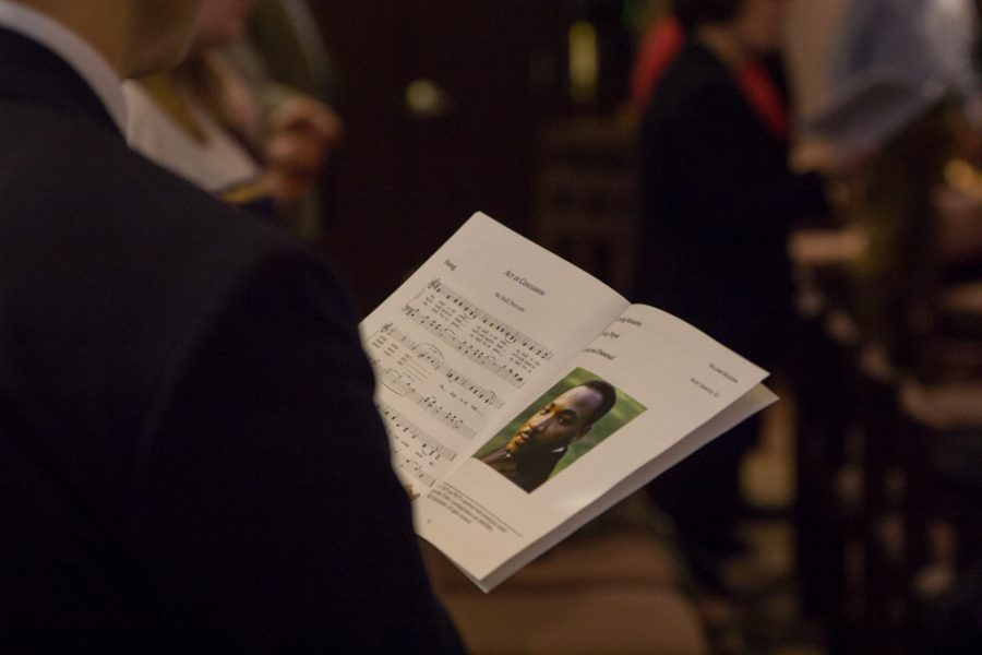 An attendee at the prayer service looks over the song, 'We Shall Overcome'.