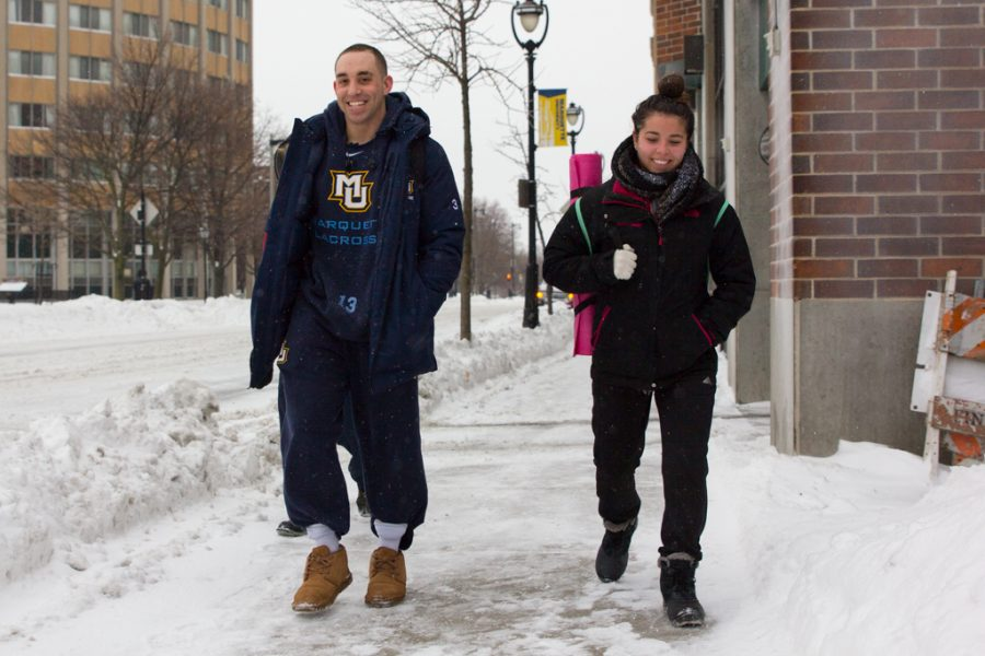 Mikey Zadroga (left), s senior in the College of Communication, and Megan Cote, a senior in the College Health Sciences, walk along 16th Street Monday morning.