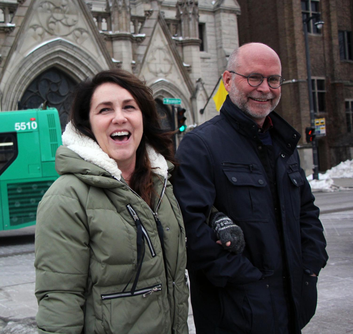 Alumna Jane Panther (left) walks down 12th Steet on Marquette's campus with her husband and alumnus Rob Panther.