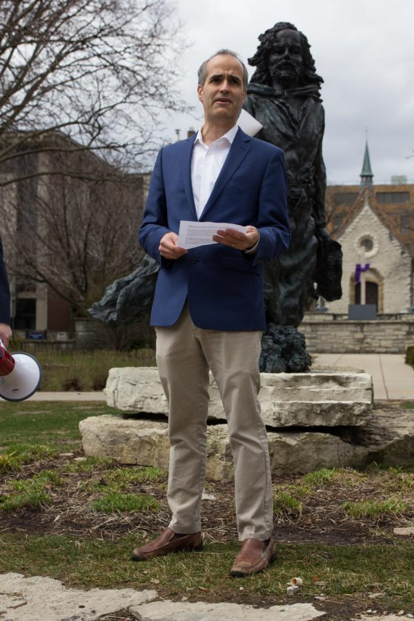 Adjunct professor Sam Harshner welcomes the crowd in front of the Father Marquette statue.