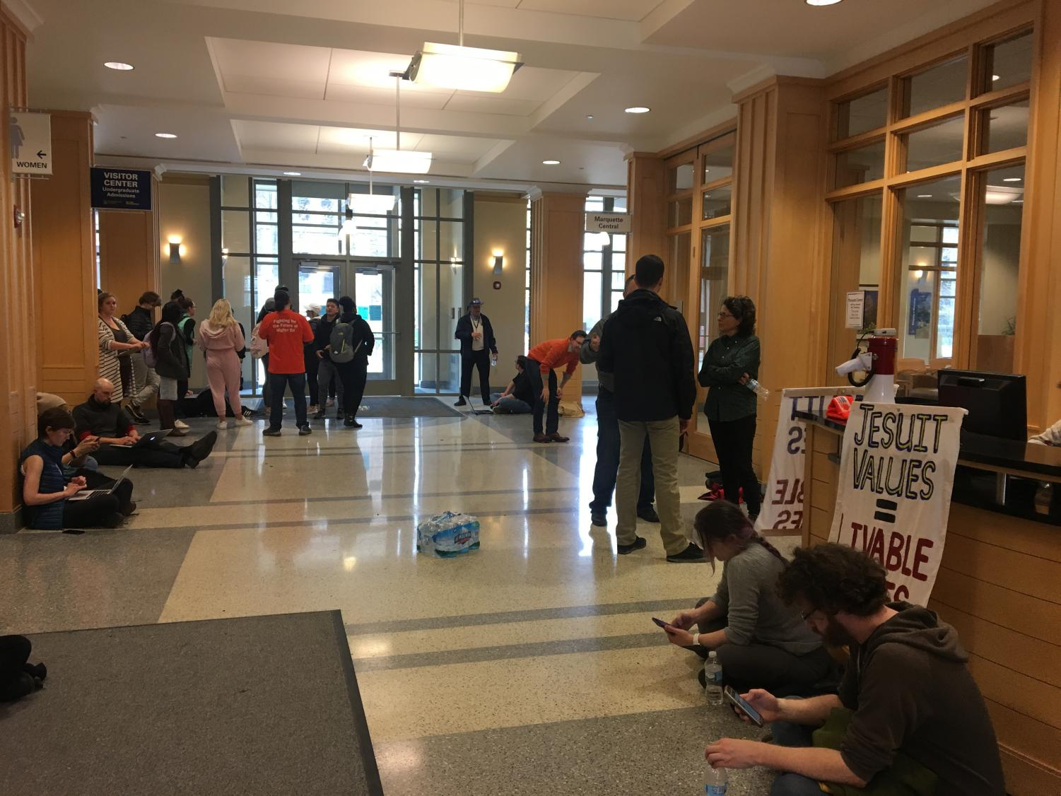 Faculty, students and community members sit in Zilber Hall awaiting for administration members to come out.