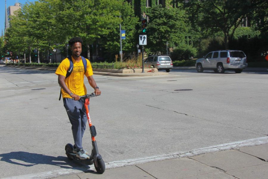 Samuel Johnson, a junior in the College of Arts & Sciences, rides his scooter down Wisconsin Avenue.