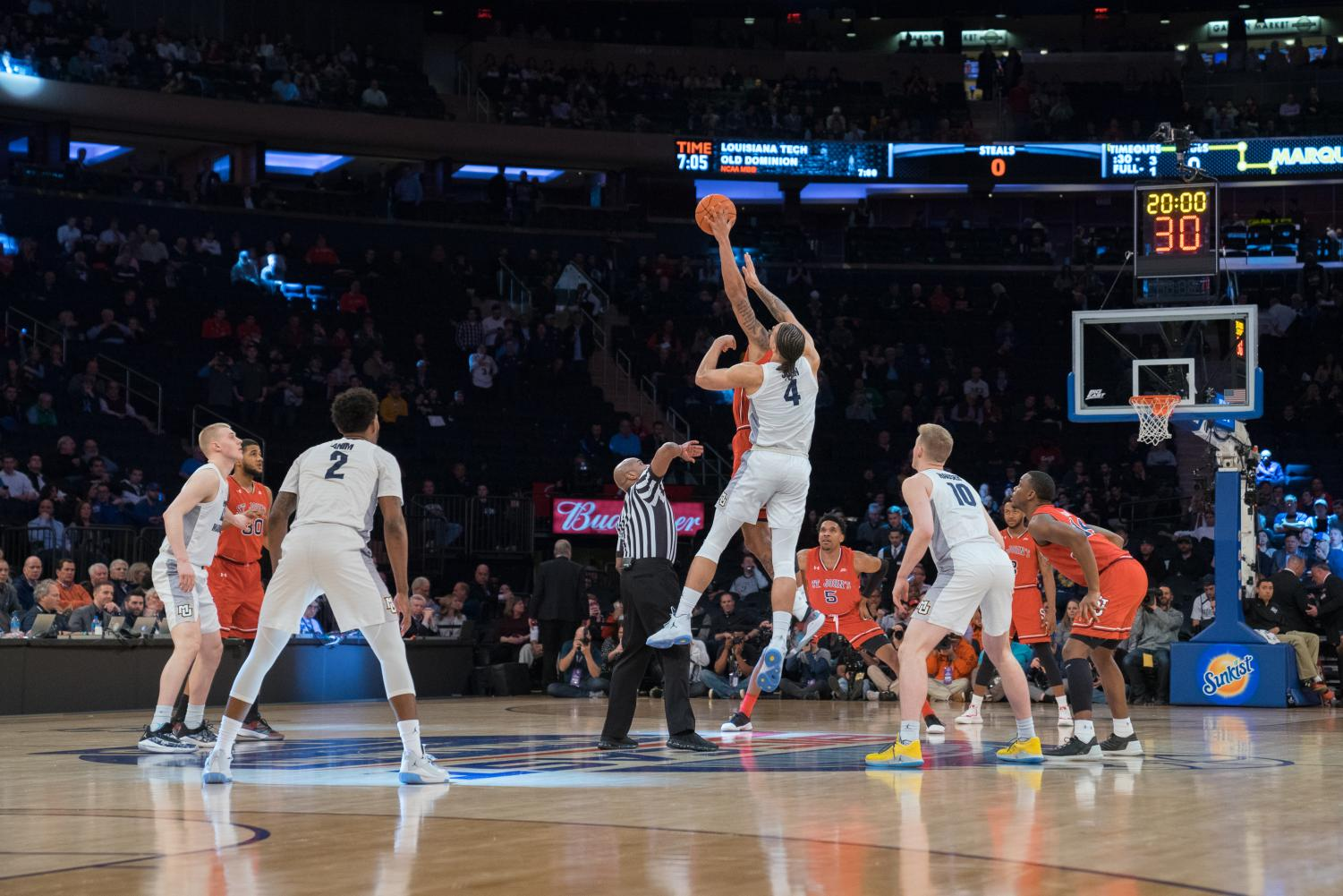 Marquette's then-sophomore center Theo John, center, tips off against St. John's in the 2019 BIG EAST Tournament.