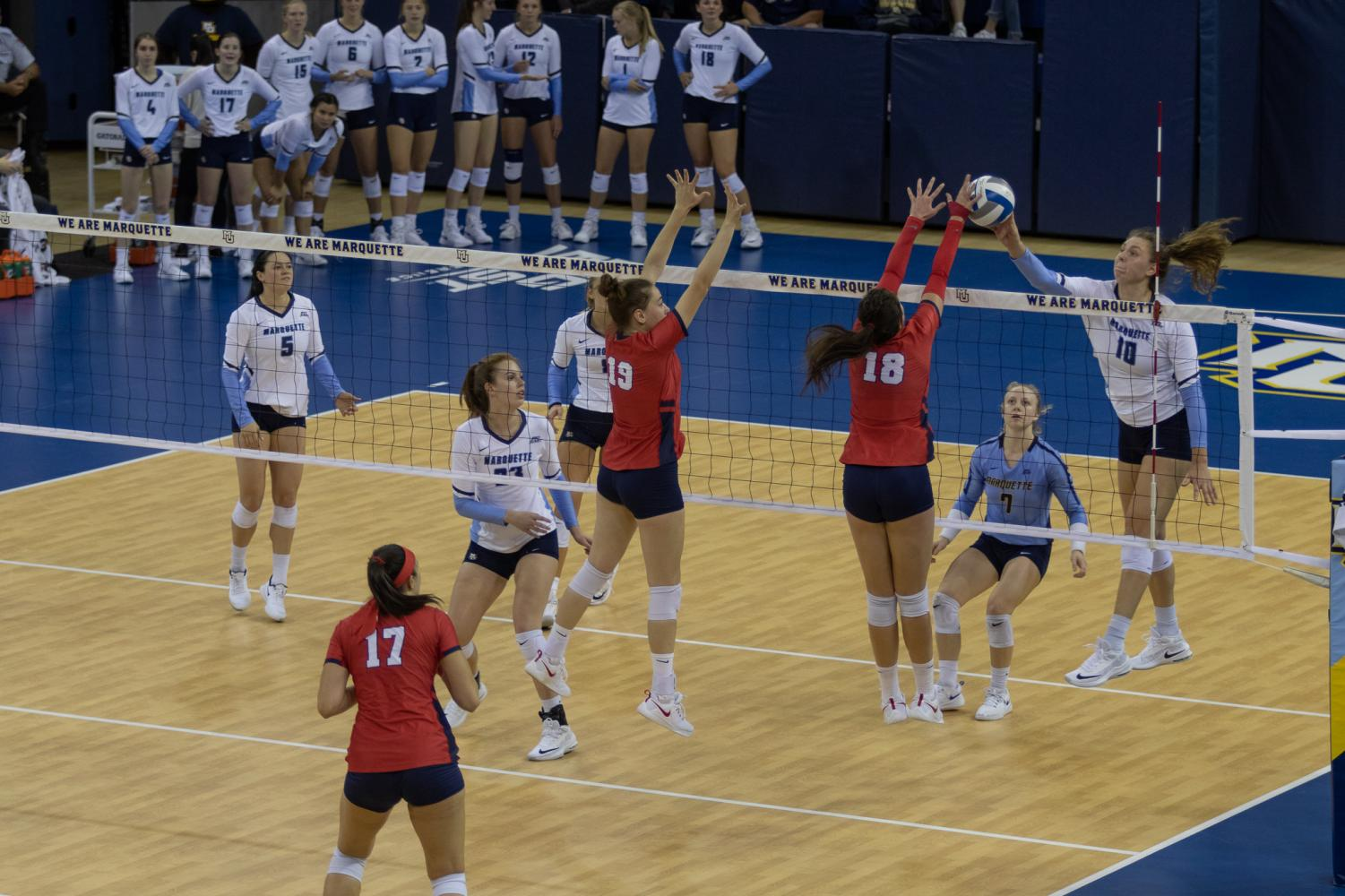 Allie Barber (far right) goes for a kill against St. John's at the Al McGuire Center.