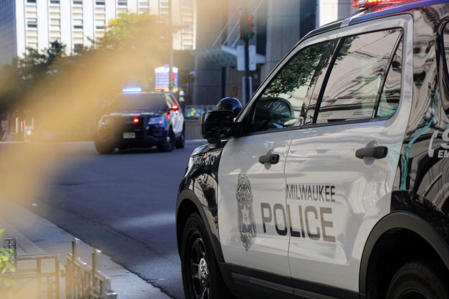 Two MPD vehicles block traffic near 9th Street and Wisconsin Avenue.