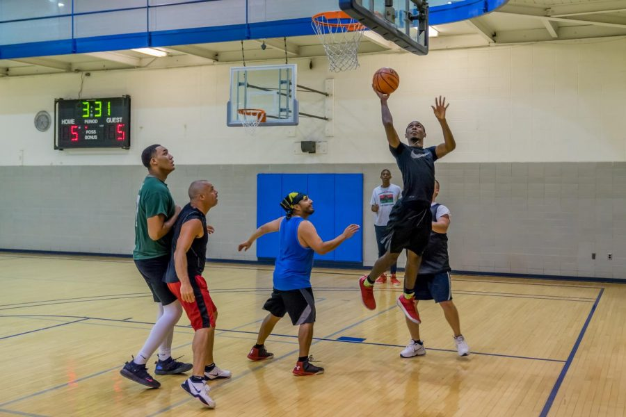 A player attempts a layup as the opposing team anticipates a rebound.